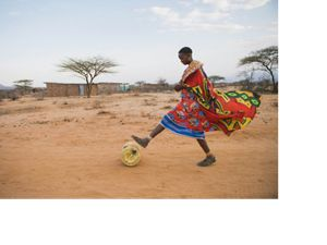 person in Kenya rolling barrel on the ground