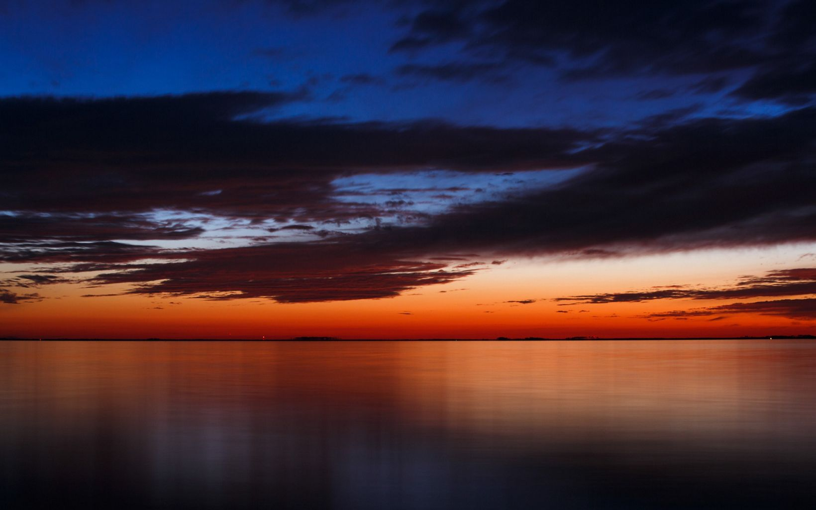 Flat water, a red sunset, and a dark blue, clouded sky.