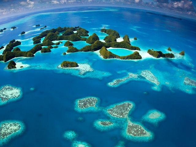 aerial view of islands and coral surrounded by tropical waters.