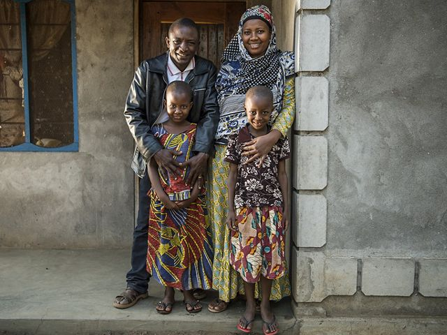 The Katunka family stands in front of their home in the village of Mgambo near Lake Tanganyika in western Tanzania. They are considered a Class One Model Household family and practice positive health and environmental behaviors and encourage their fellow community members to adopt these behaviors in their own households.