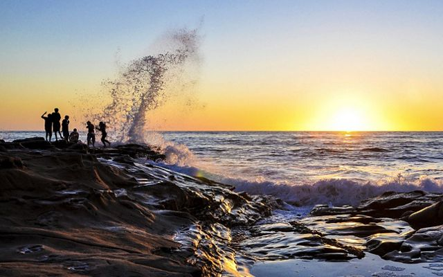 People standing on a rocky shore in the distance at sunset as waves crash on the rocks.