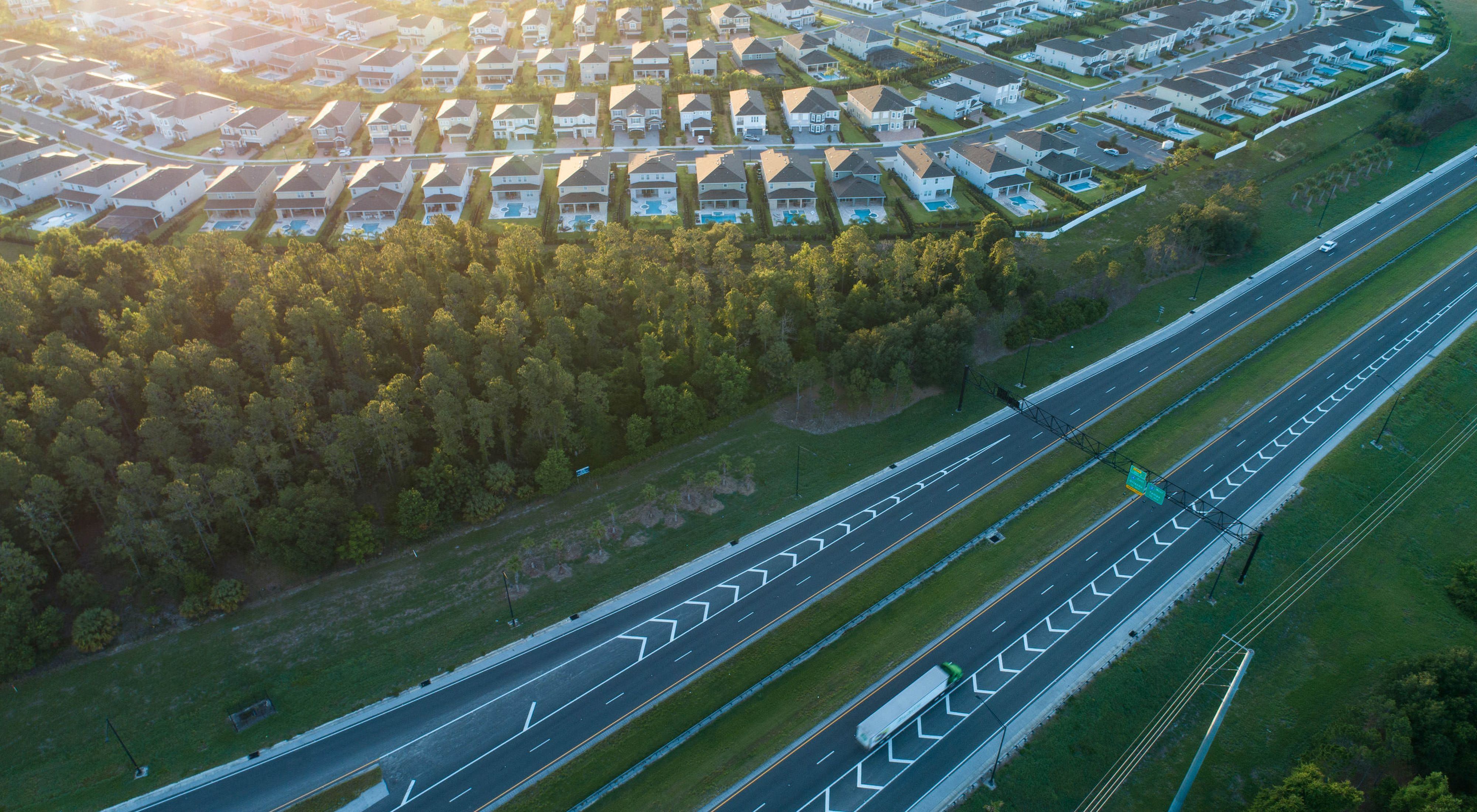 An aerial photo depicting new  housing development sprawling outward from Orlando, Florida, near where the State Road 429 (a toll road)  branches north from Interstate 4.  The development, named Reunion, is adjacent to Reedy Creek, which is one of the most narrow and fragile threads of wildlife habitat in the statewide Florida Wildlife Corridor. May 2019.