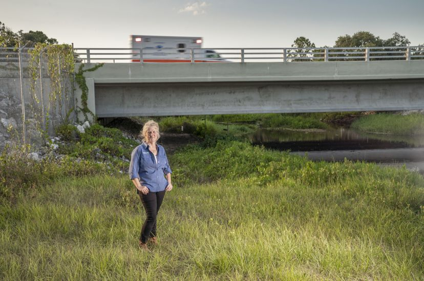 woman stands on grassy riverbank under a highway as an ambulance drives by