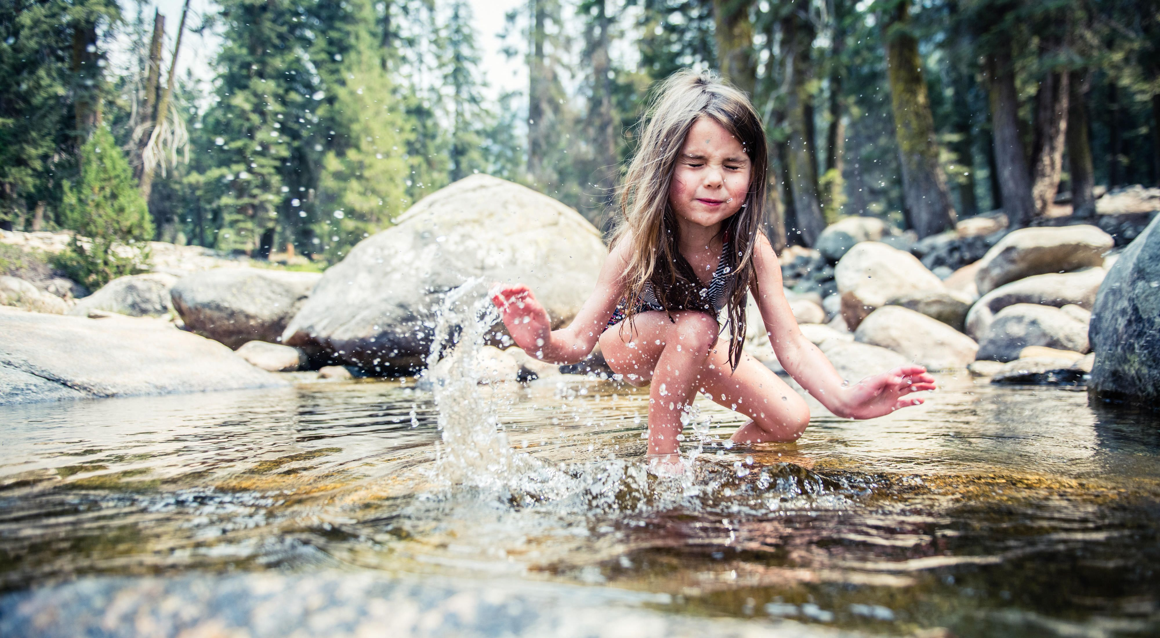 A girl splashes water in front of rocks.
