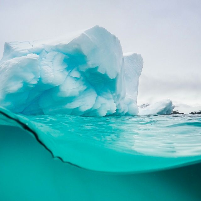 Half view under and above the surface of an iceberg in Antarctica