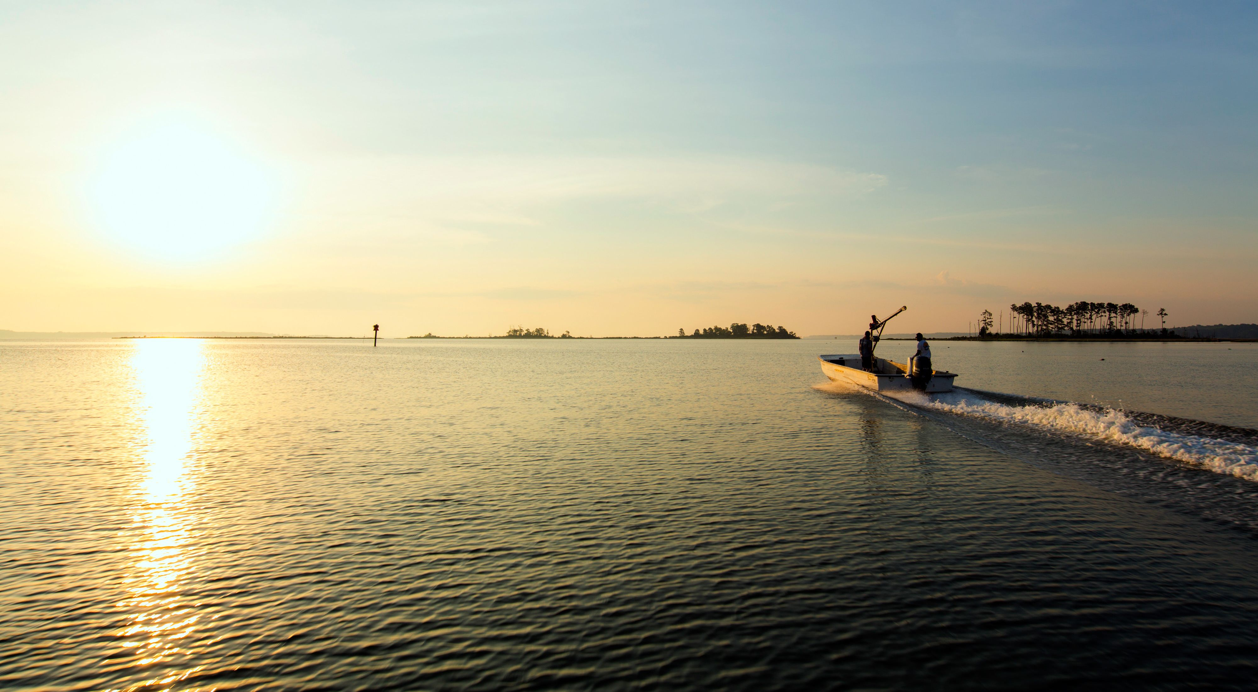 Two men in a flat bottomed jon boat motor into the open water of the Chesapeake Bay. The rising sun reflects off the calm water.