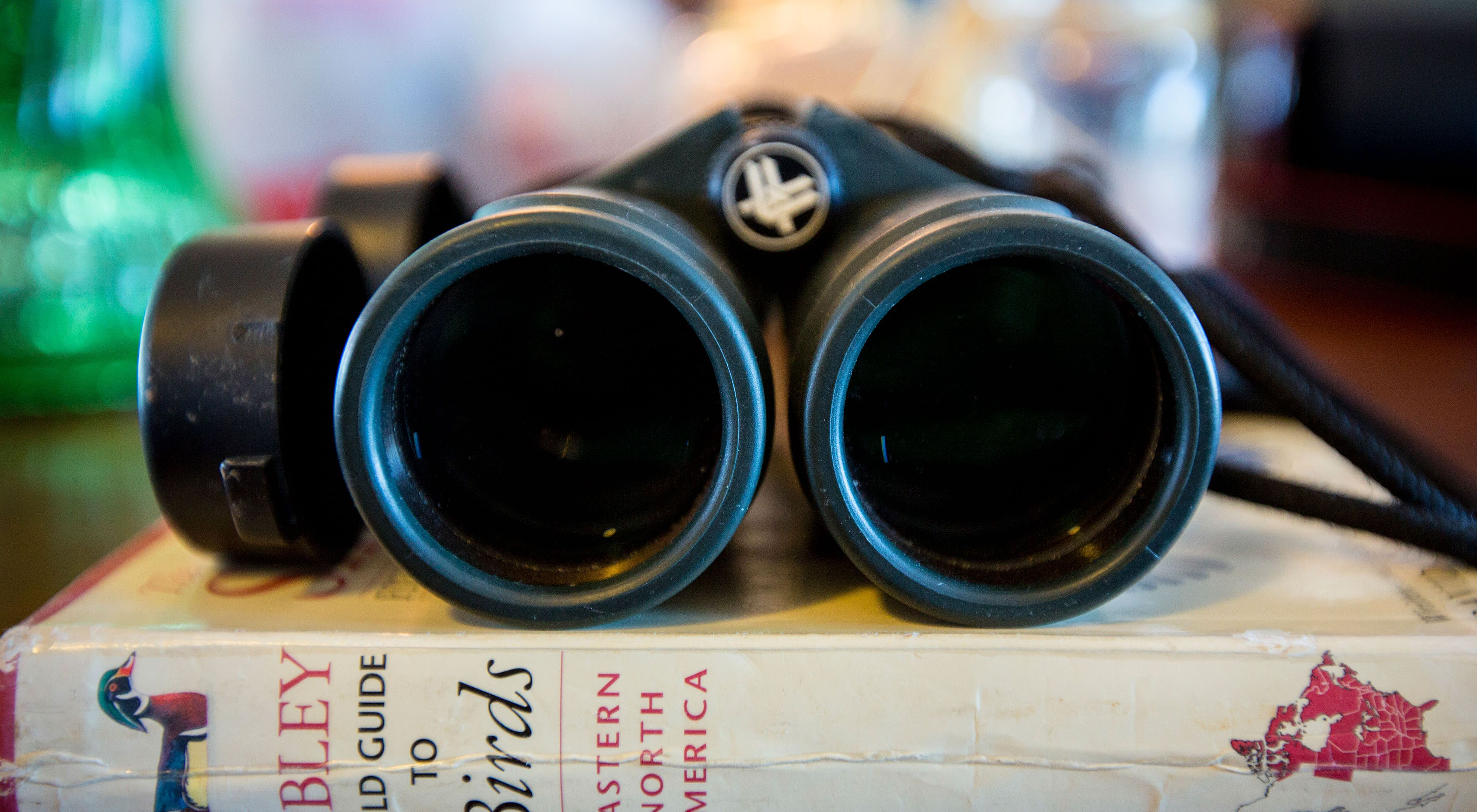 A pair of binoculars sitting on a stack of books, with the large lenses facing the viewer.