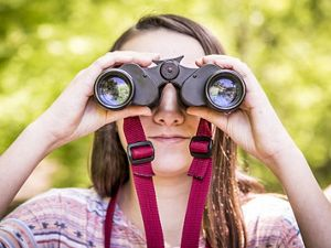 Girl holding binoculars up to her eyes, looking at the camera.