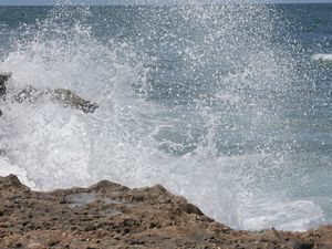 Ocean water explodes into the air against a rocky shoreline.