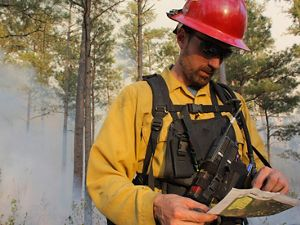 A man wearing yellow fire protective gear and a red helmet reviews a map during a controlled burn at Warm Springs Mountain. Thick smoke rises in the air behind him.