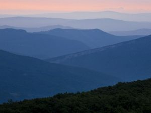 Blue mountain ridgetops roll across the landscape ending at the pink horizon.
