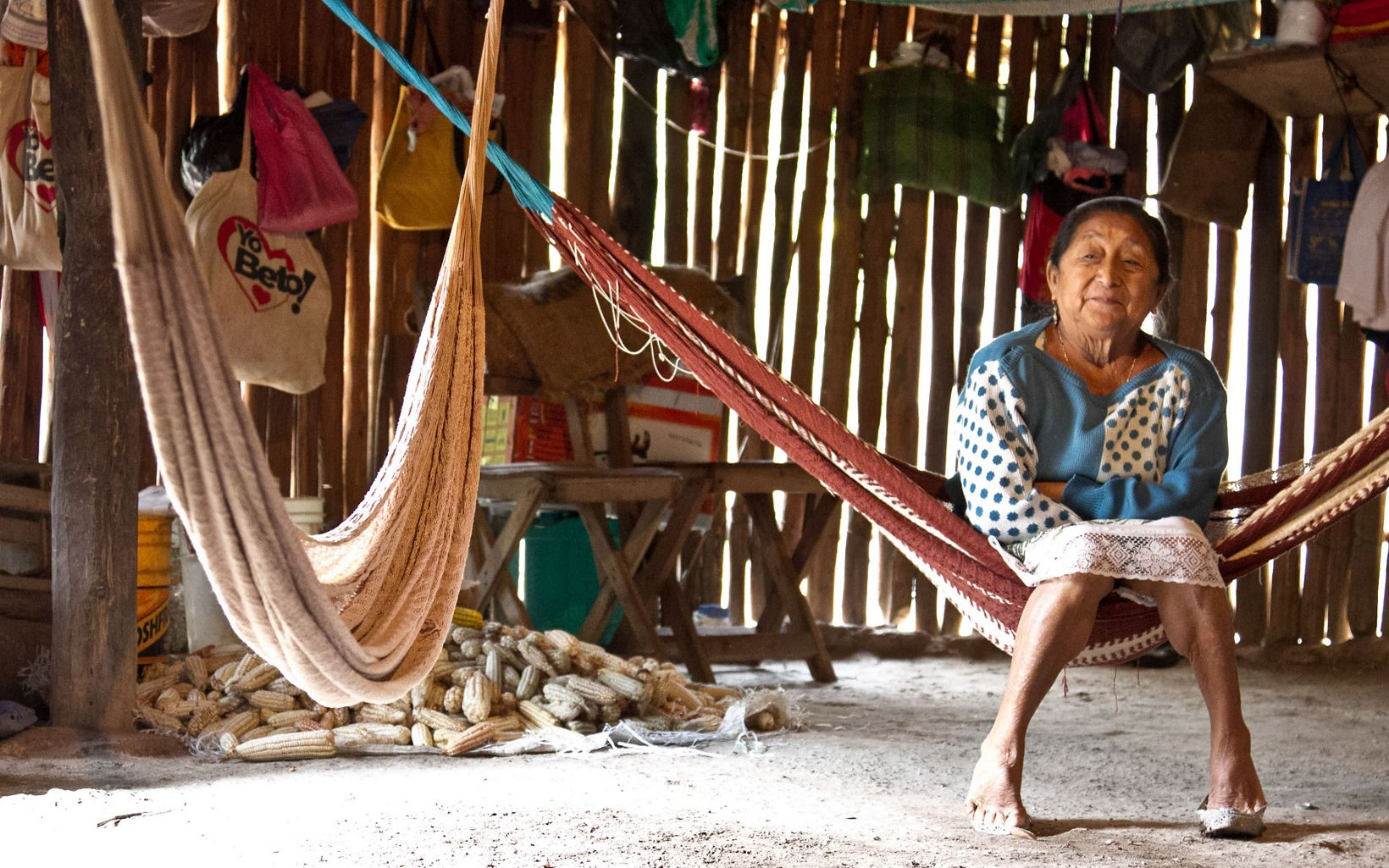 A woman relaxes in a hammock, Quitana Roo, México. In the Bethania ejido, where many families cook their food over an open fire in traditional thatched-roof homes that do not have toilets or running water, The Nature Conservancy has worked with partner Organizacion de Ejidos Productores Forestales de la Zona Maya S.C., to support sustainable forest management and income-producing activities. In the past, Bethania sold standing timber from their forests to logging companies to harvest. But now, by learning forestry and carpentry skills, ejido members can create jobs, eliminate the middle-man and sell finished wood products for a higher price.