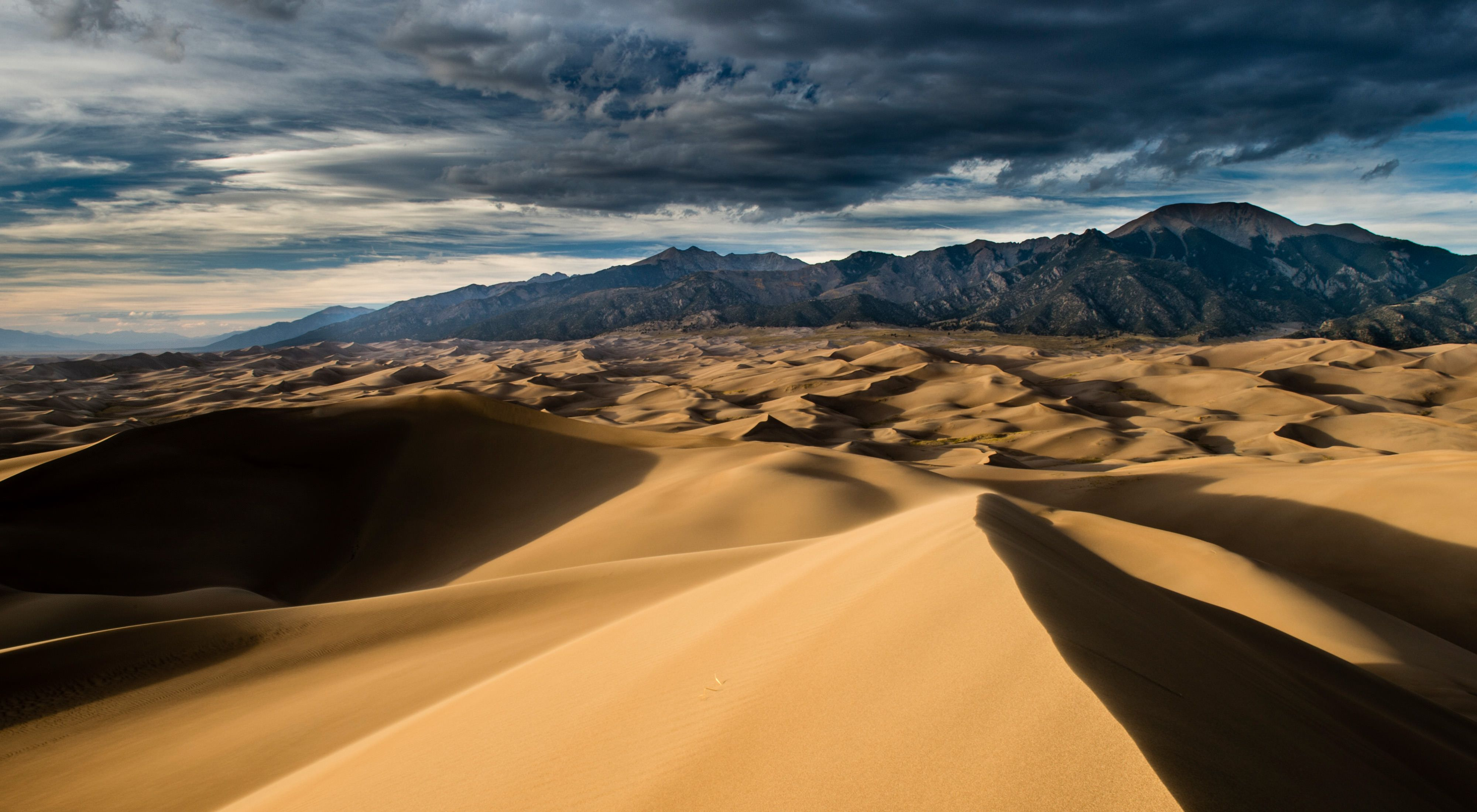 sand dunes with mountains in the background