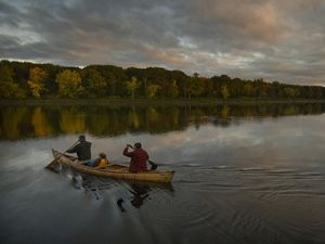 Canoe paddlers cross a quiet Penobscot River