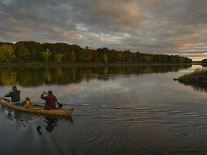 At dawn, Penobscot Tribal members Butch Phillips, his son Scott Phillips and Scott's daughter, Sage Phillips, paddle a birch bark canoe past Indian Island on the Penobscot River in Maine.