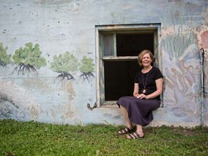 Robyn James sits in windowframe of stone building
