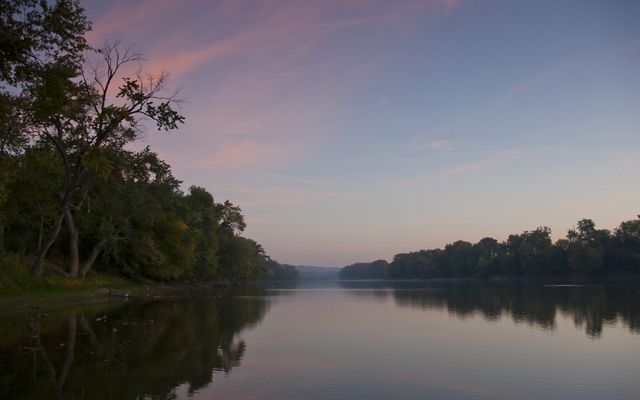 A view of the flat Wabash River during sunset.