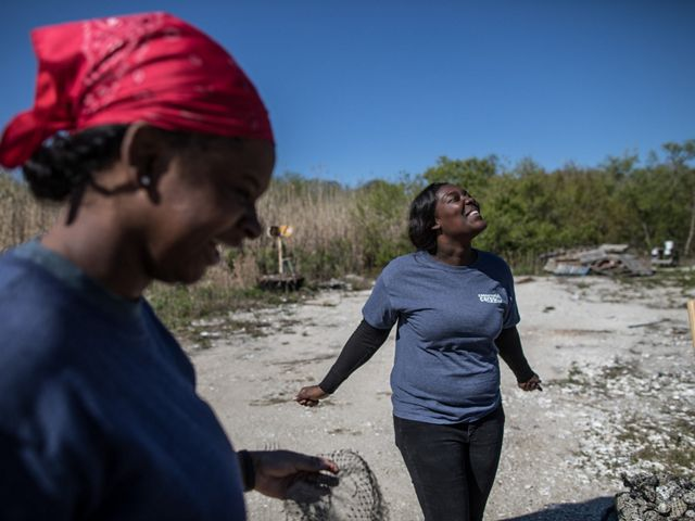 Conservation Corps member Dee Dee, 21, shares a laugh with her colleague, Myesha Campbell, 20, while creating natural seawall barriers using old oyster shells.