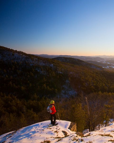 A snowshoer stands at the top of a snowy mountain overlook.