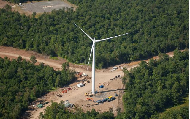 a wind turbine surrounded by construction equipment