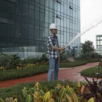 An employee waters the rooftop garden on the Tencent Binhai towers in Shenzhen, China. November 2017. Environmental features of the Tencent Binhai towers in Shenzhen, China include rooftop gardens on the three skybridges, permeable surfaces to slow rainwater on the two towers' topmost roof and many of the landings and ground level, solar panels and 'smart rooms' that adjust temperature based on how many people are in them. TNC's Build Healthy Cities Program.