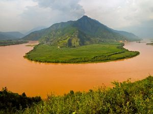 Heavy rains turn the river a muddy-brown as viewed above a bend in Yunnan province, southwestern China.