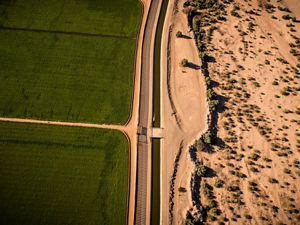 An irrigation canal divides green U.S. farmland and the dry Sonoran desert by the USA/Mexican border.