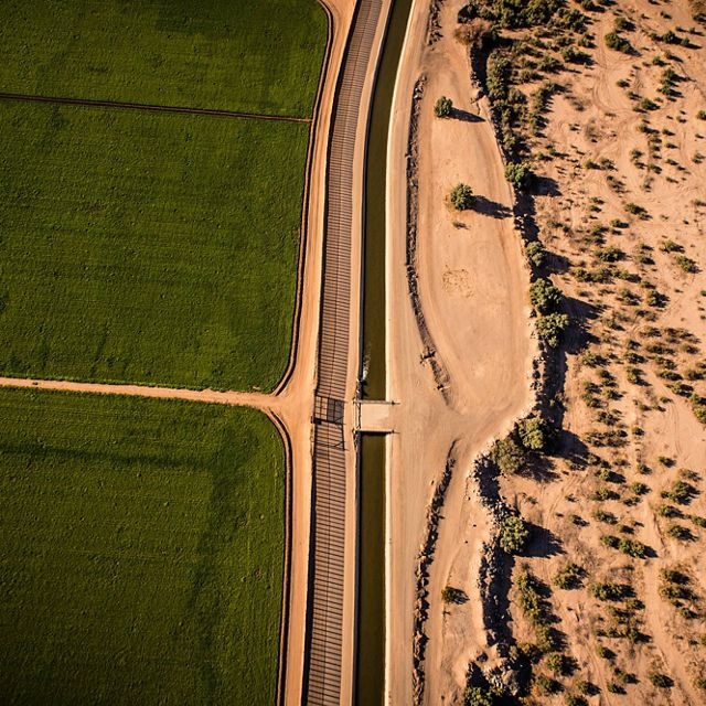 Green U.S. farmland separated from the dry desert by the USA/Mexican border and an irrigation canal.