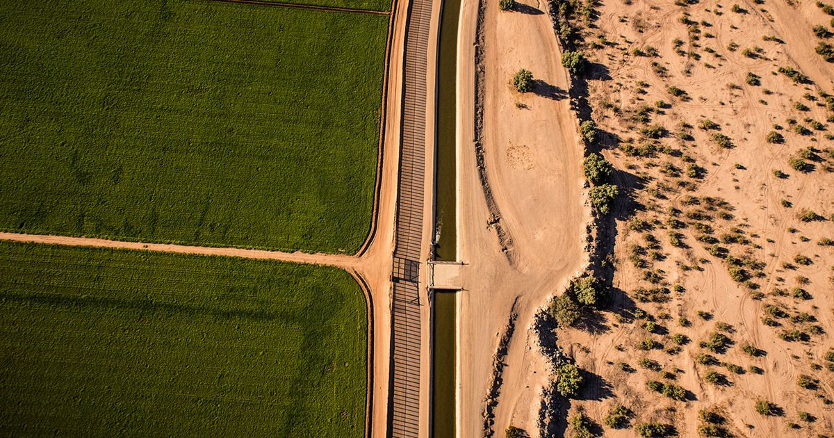 aerial view of green farmland next to dry desert land