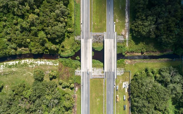 An aerial photo of State Road 80 near LaBelle, Florida. Beneath the bridge in the photo is a wildlife underpass that is used for safe passage by a variety of wildlife. TNC Florida worked with the Florida Department of Transportation to establish this underpass that connects land easements on both sides of the road and establishes a path for animals to travel. May 2019.