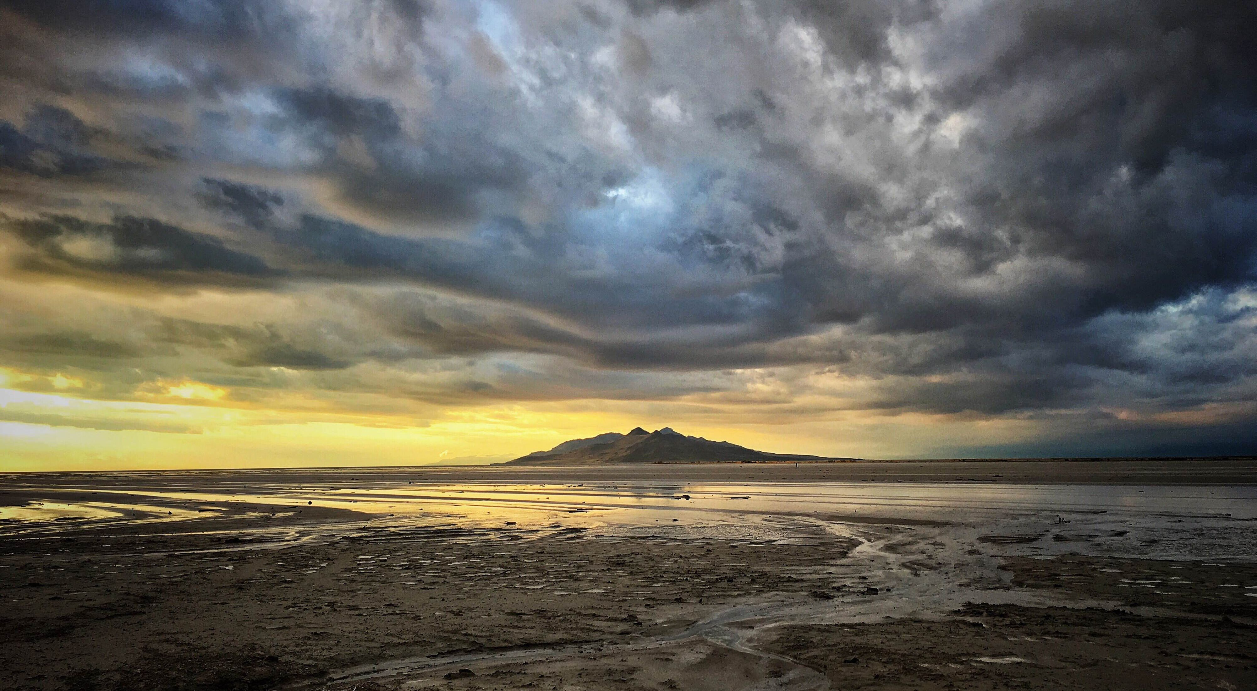 Shallow water in the great salt lake under dramatic cloudy skies with a hill in the distance.