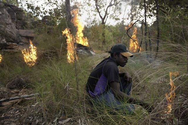 A man from an indigenous community in northern Australia starts a controlled burn in grasslands.