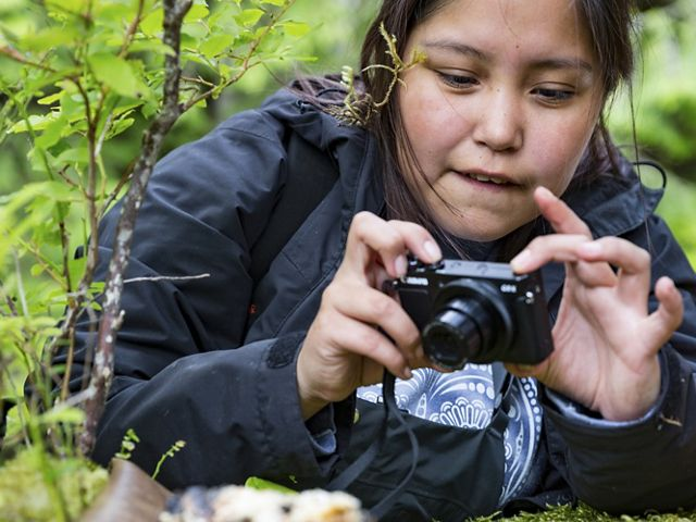A girl takes a photo as part of a photography workshop