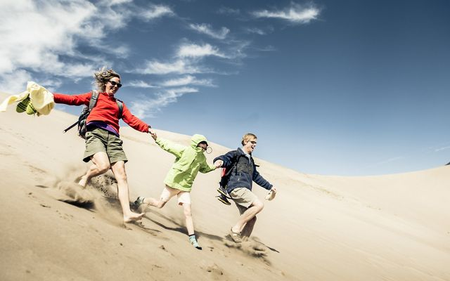 A family runs down the dunes at Great Sand Dunes National Park