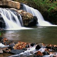 A waterfall flows over big brown boulders.
