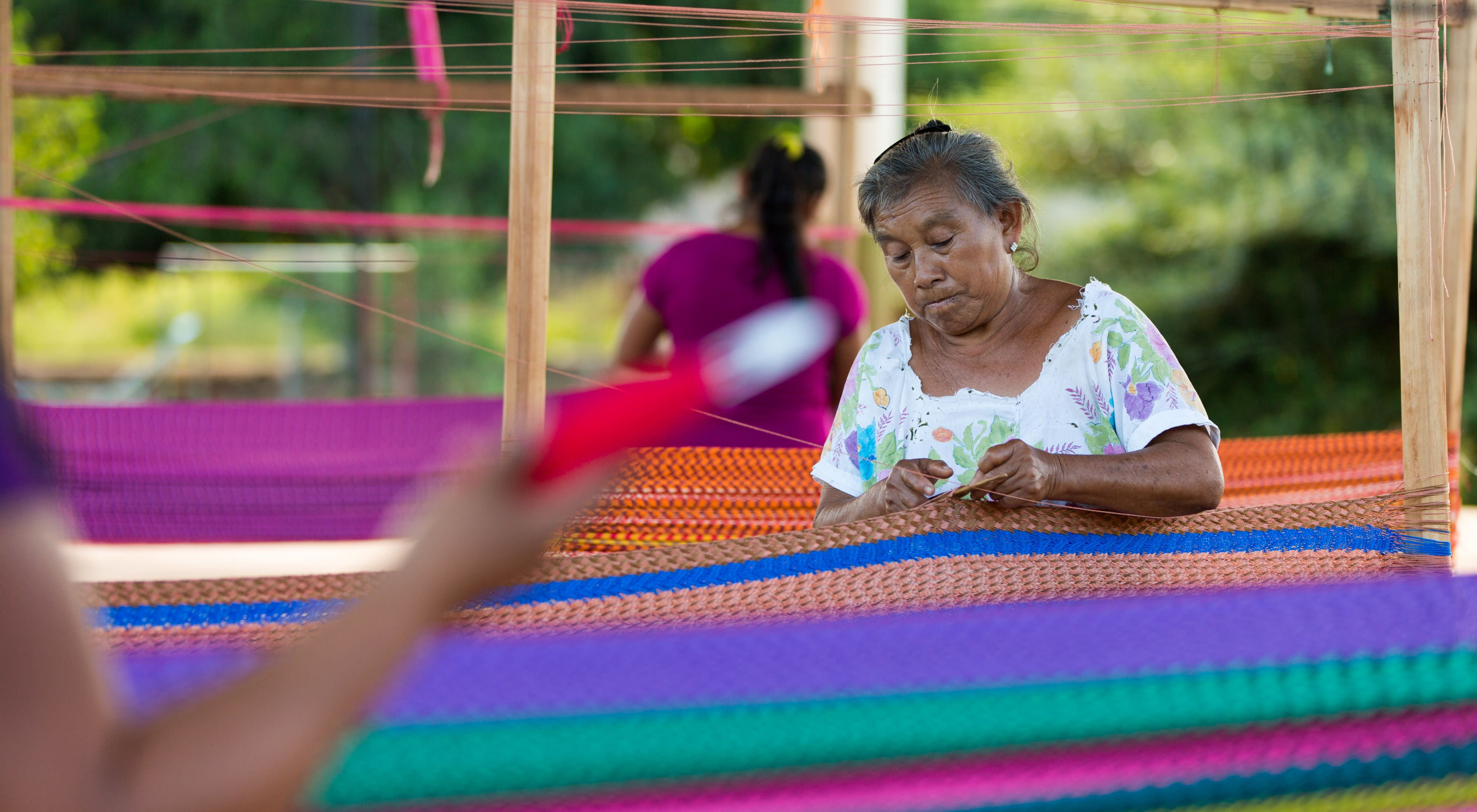 Woman weaving traditional Mayan hammock.