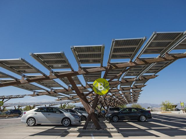 Cars parked under the shade of solar panels.