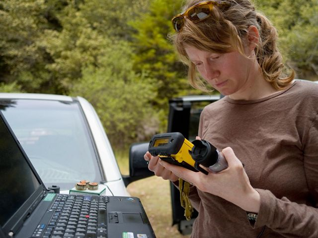 Jennifer Carah, an applied scientist on the The Nature Conservancy's California staff, checking logging devices she uses to record and collect water temperature data.