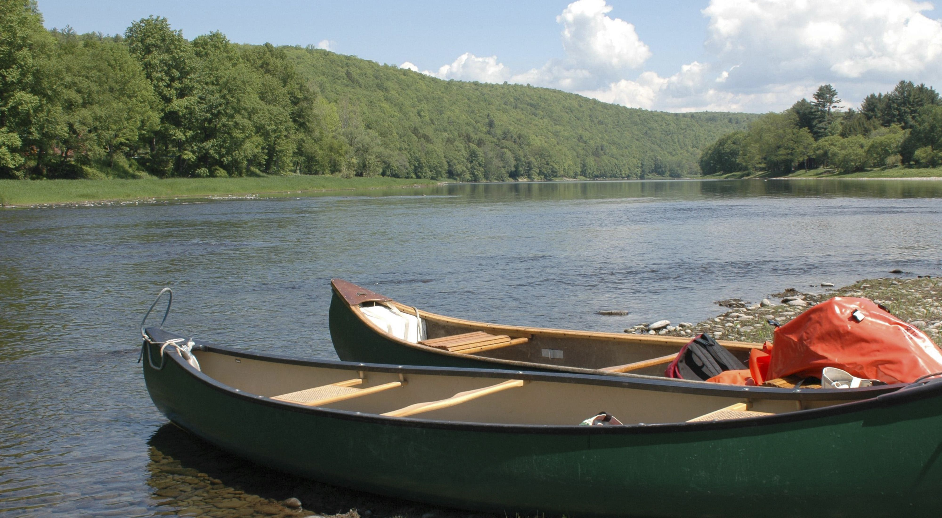 Two canoes sit on the side of a river bank.