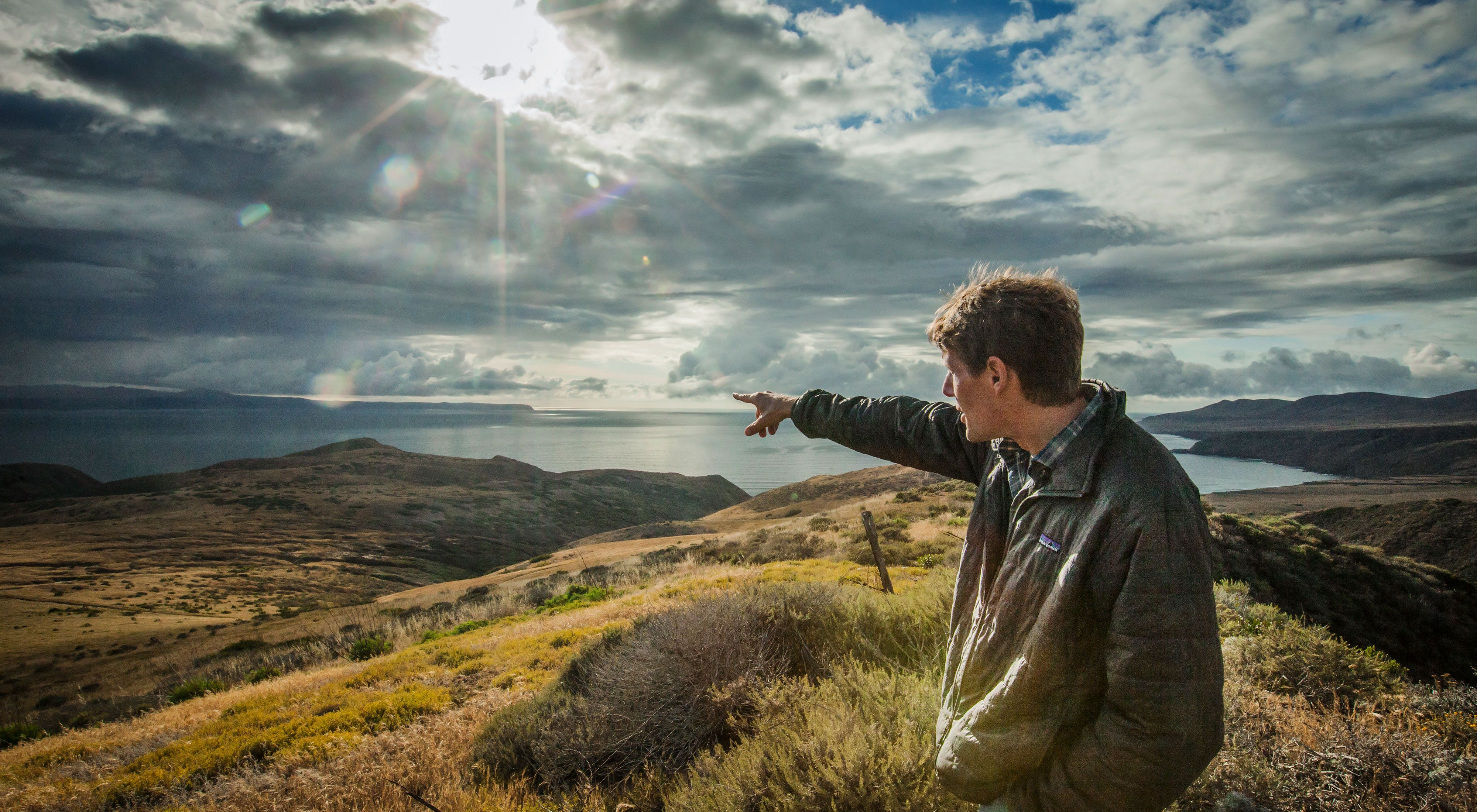 Scott Morrison, The Victor E. Shelford Director of Conservation Science for The Nature Conservancy, stands at the western edge of Santa Cruz Island overlooking Santa Rosa Island in the distance.