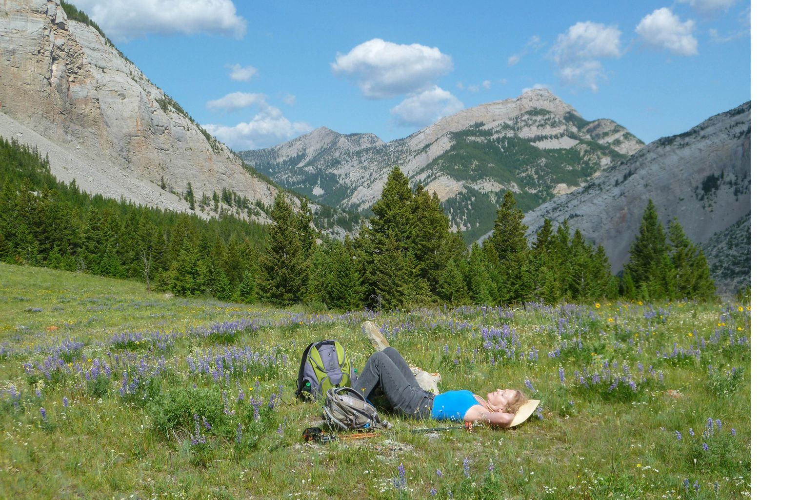 A woman relaxes in a meadow at The Nature Conservancy's Pine Butte Guest Ranch.