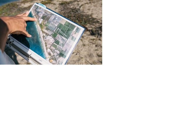 hands holding a binder with a aerial map of a coastal community