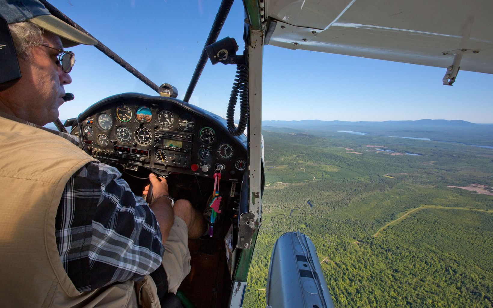 A birds eye view of the Maine landscape from the seat of a plane.