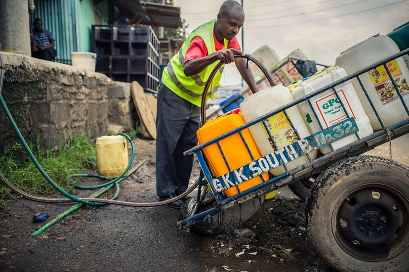 Man filling up water containers in Nairobi, Kenya.