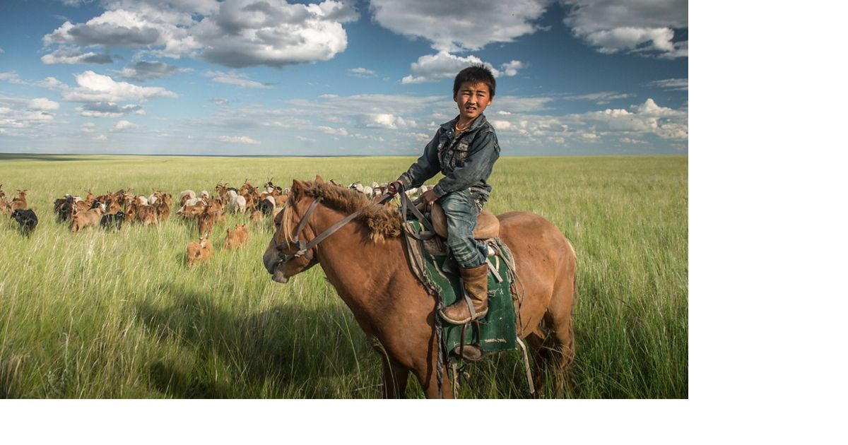A young boy on horseback minding his family's herd of goats in the grassland steppe of eastern Mongolia's Tosonhulstai Nature Reserve.