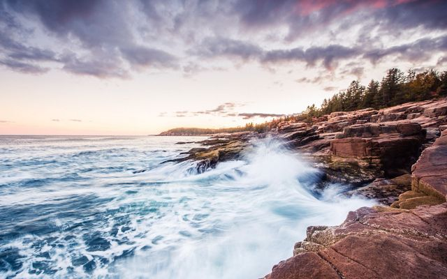 Waves crashing against the rocky coast of Acadia National at sunset in Maine.