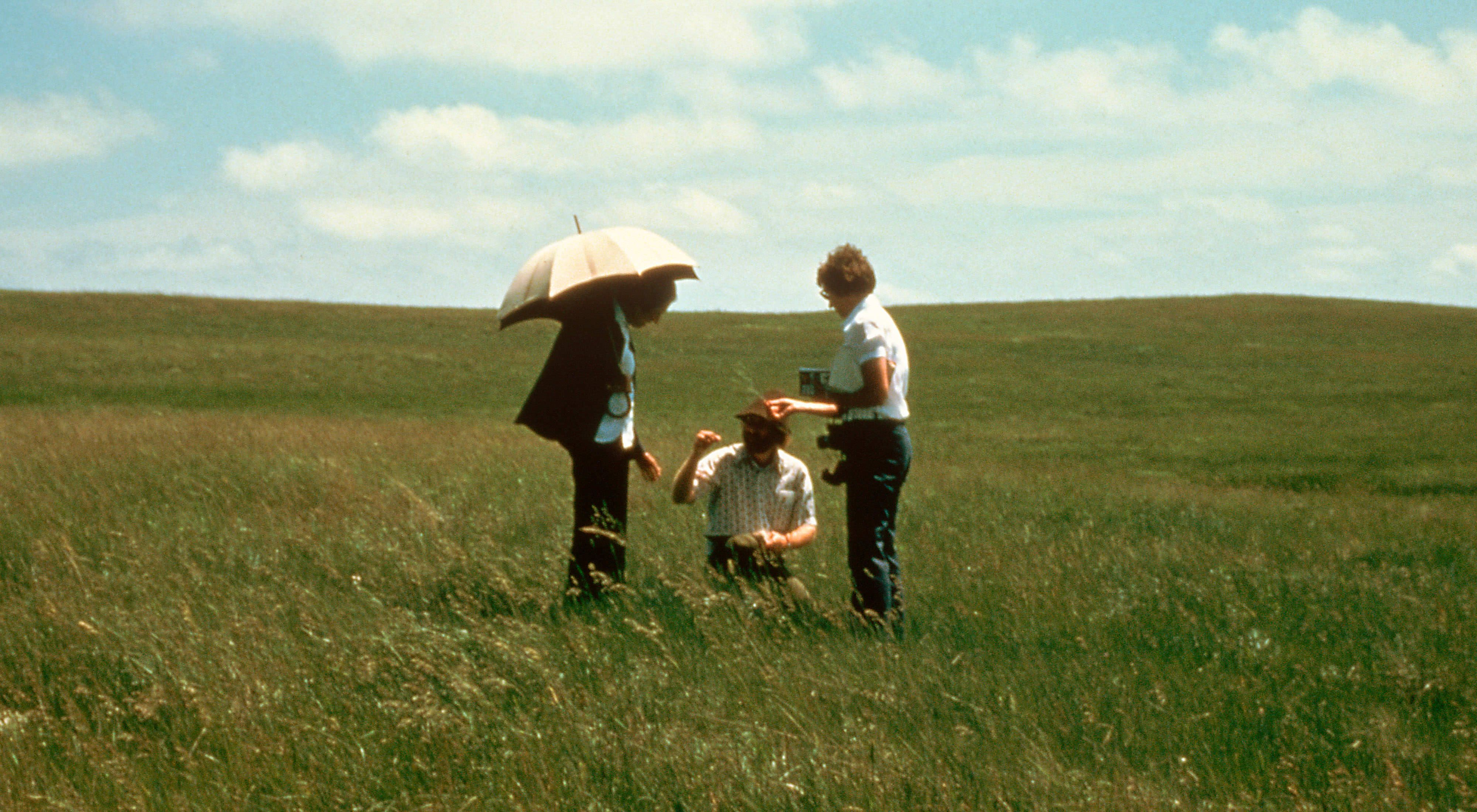Katharine Ordway (holding umbrella) with Goeff Barmard (kneeling) and a unidentified individual study prairie grass in the Ordway Prairie Preserve