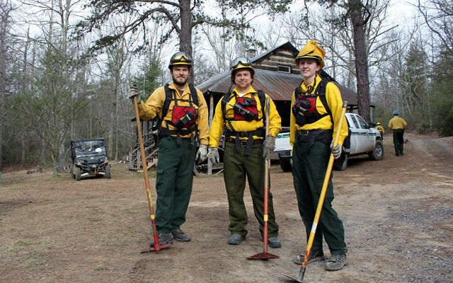 Three fire team members standing together.