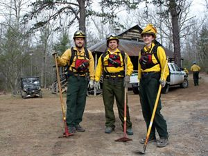 Three people wearing yellow fire gear stand in front of a rustic lodge during a controlled burn.