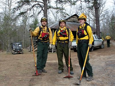 Three people wearing fire gear pose together.